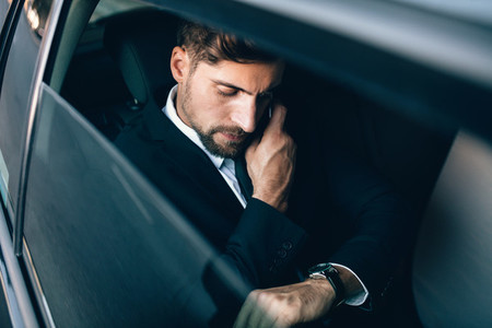 Businessman travelling by car checking time and talking on cellp