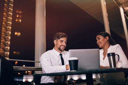 Business couple waiting for flight at airport cafe