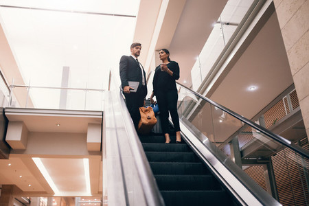 Business traveler with baggage on the escalator at the airport