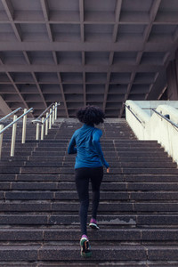 Back view of woman running up the stairs