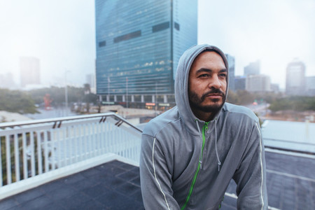 Portrait of a male runner in hooded sweatshirt