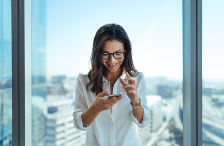 Happy businesswoman using her mobile phone at office