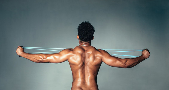 Muscular young man stretching arms with rubber band