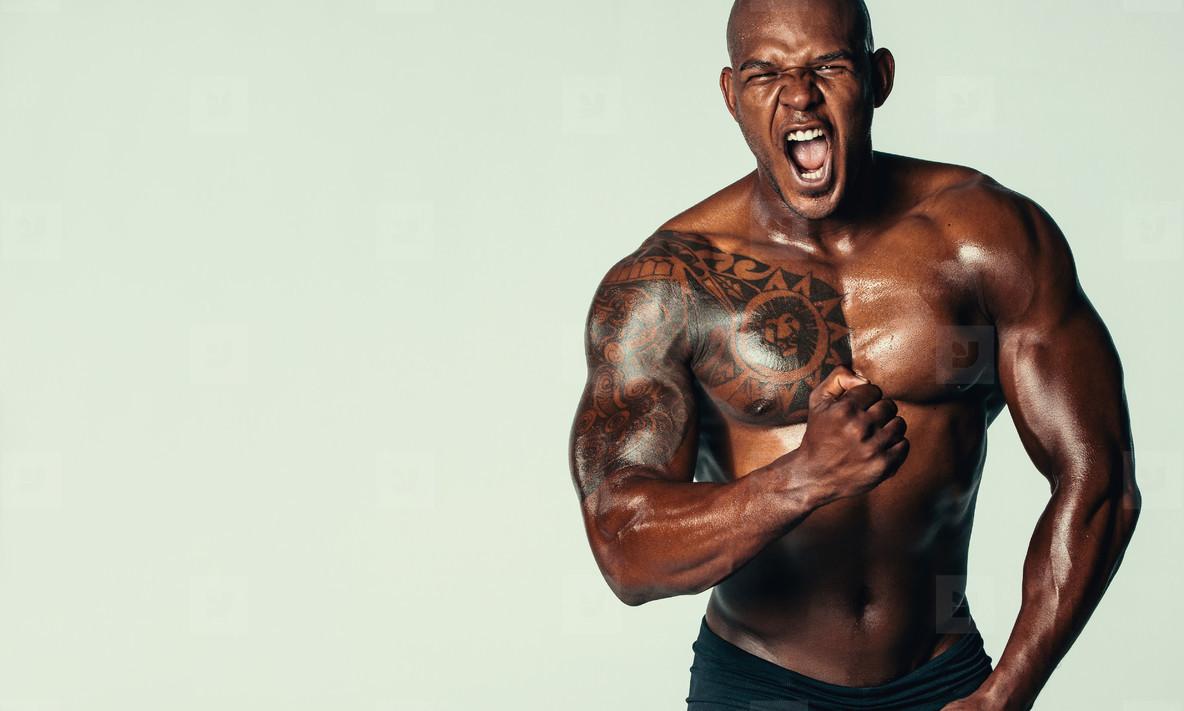 Aggressive bodybuilder screaming against grey background