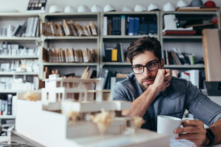 Thoughtful male designer looking at model with cup of coffee