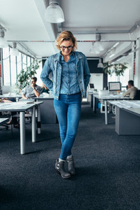 Businesswoman standing in office and looking down