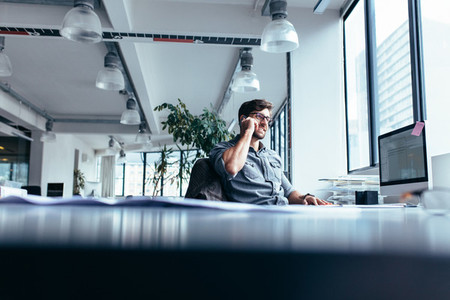 Young businessman talking on cellphone in modern office