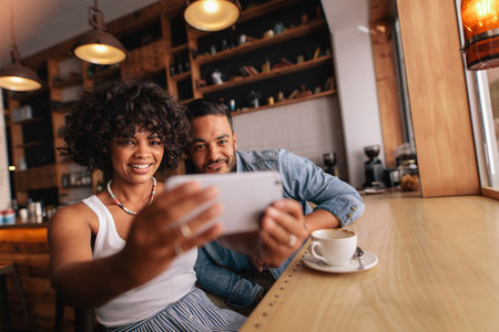 Beautiful young couple at cafe taking selfie with mobile phone