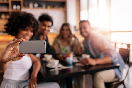 Group of friends at cafe taking selfie