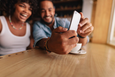 Young couple sitting together at cafe and taking selfie