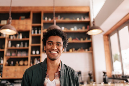 Handsome young african guy standing in a coffee shop and smiling