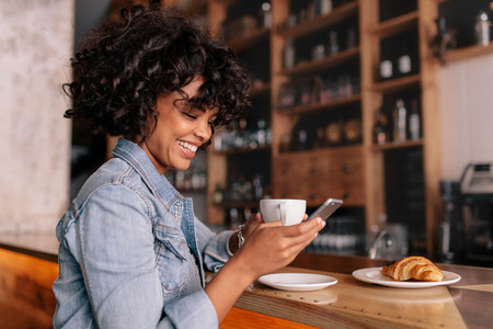 Smiling woman using smart phone in a modern cafe