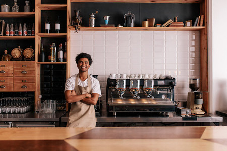 Barista in apron looking at camera and smiling