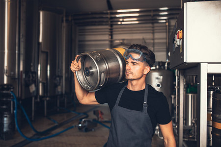 Brewer with large metal container at brewery factory