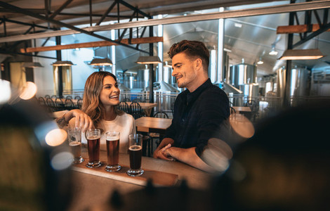 Couple at brewery bar and tasting beer