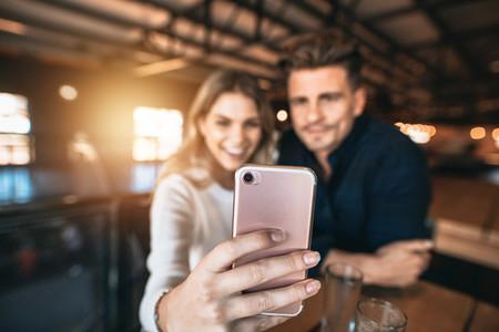 Couple taking selfie at bar