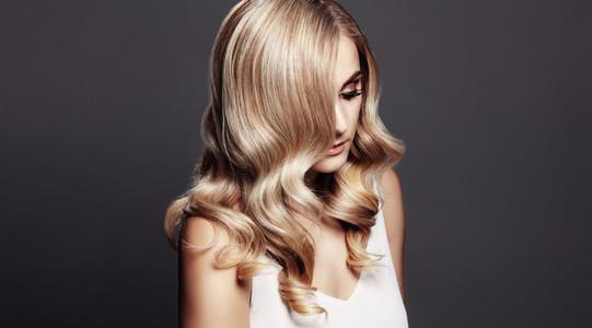 Elegant woman with shiny wavy blond hair