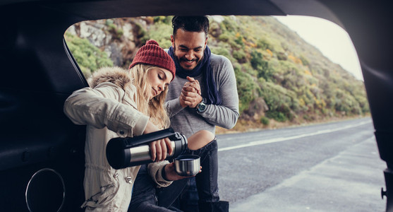 Couple on road trip having coffee break