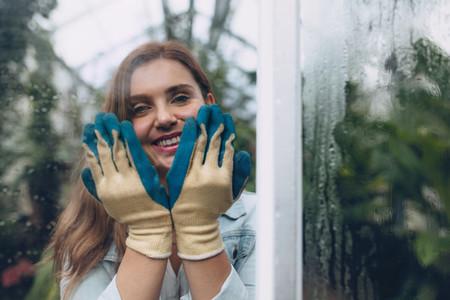 Happy female gardener in plant nursery