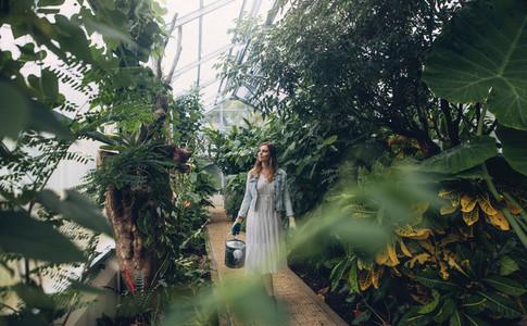 Gardener with watering can walking in botanical garden