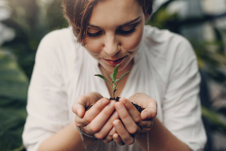 Woman smelling small plant in garden center