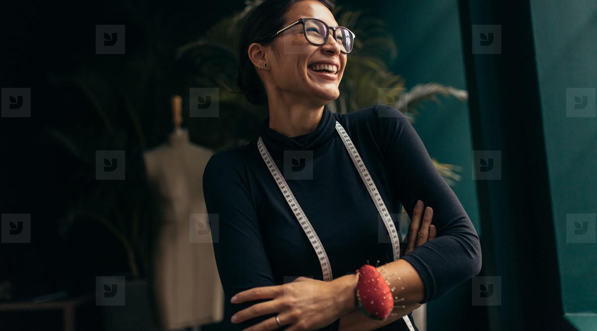 Female fashion designer laughing in her studio