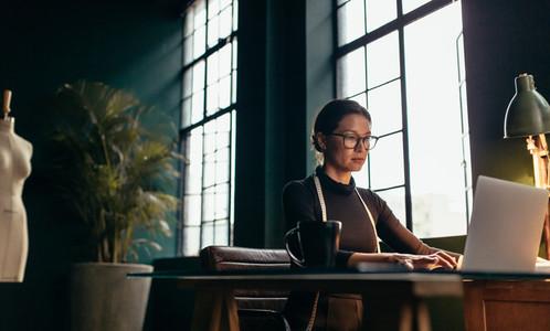 Fashion designer using laptop at her office desk