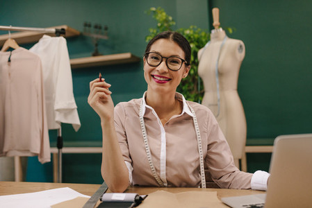 Female fashion designer sitting at desk and smiling