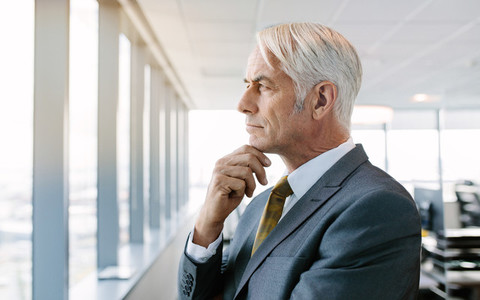 Thoughtful senior businessman standing by window