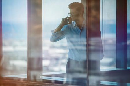 Mature business man standing inside office using cellphone