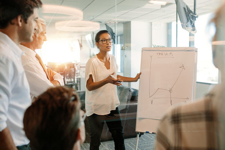 Businesswoman explaining graph to colleagues in office