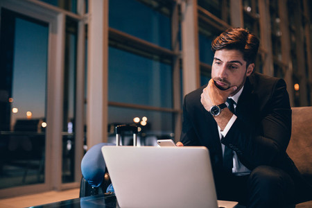 Businessman waiting at airport lounge and looking at laptop