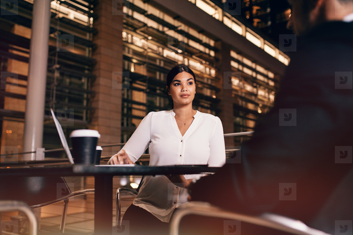Businesswoman sitting at cafe in airport table with businessman