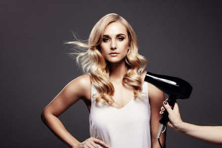 Gorgeous blond woman in a studio with hair dryer