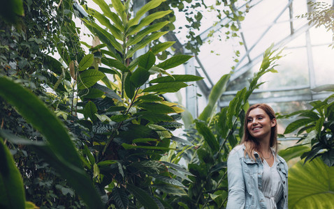 Smiling female standing in greenhouse