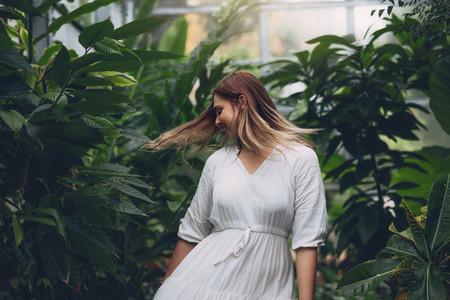 Beautiful female fashion model in greenhouse