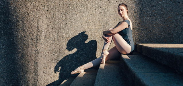 Ballet dancer sitting on stairs wearing pointe shoes
