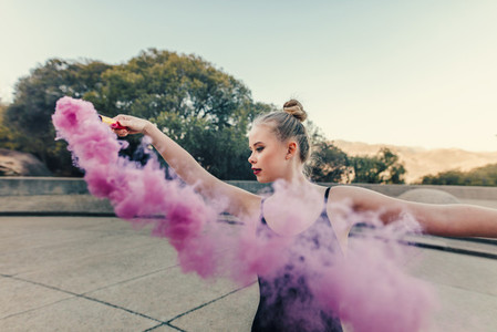 Female ballet dancer practicing dance moves using a smoke bomb