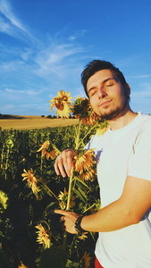 Young man hugging a sunflower