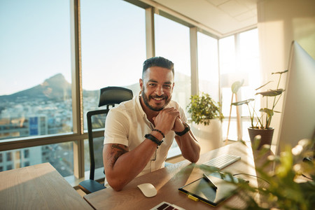 Male designer sitting at his desk and smiling