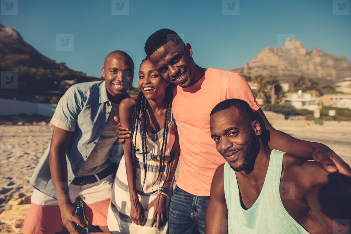 Group of friends taking selfie on the seashore
