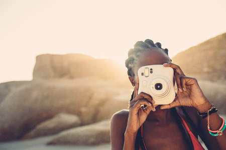 African american female taking pictures on the beach
