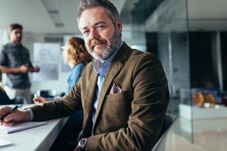Mature businessman sitting in meeting room