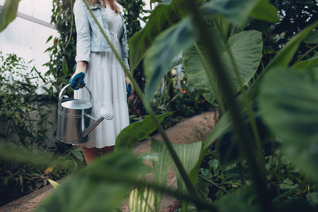 Woman with watering can in greenhouse