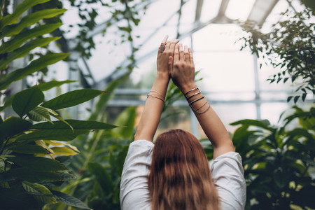 Female model standing inside greenhouse