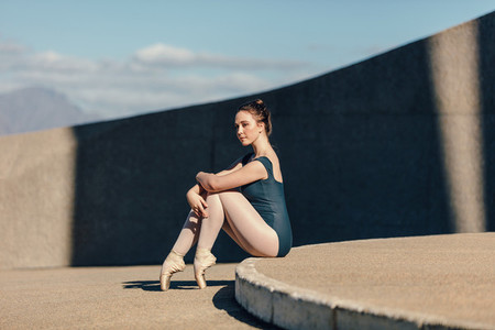 Female ballet dancer sitting gracefully while resting her toes o