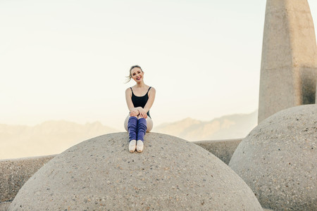 Female ballet dancer sitting near a monument