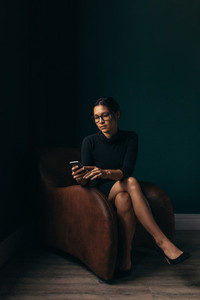 Sophisticated woman on chair using mobile phone