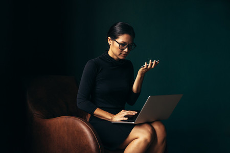 Businesswoman using mobile phone and using laptop