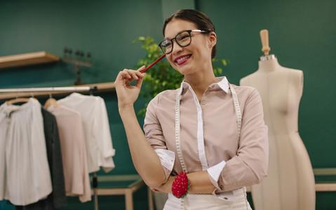 Female dressmaker standing in studio with smile